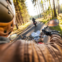 driver's view on motorcycle riding in forest with other motorcyclist