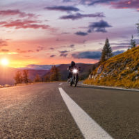 Motorcycle driver riding with light surrounded by mountains