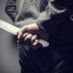 Person holding knife behind their back out of sight