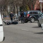 Accident in the city: a broken motorcycle and a car. Registration of a traffic accident. Traffic jam due to an accident, police car, police, people
