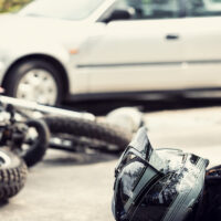 Dead motorcyclist on the road after traffic incident with a car