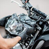 Worker repairing motorcycle headlight in the workshop