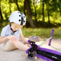 Toddler boy in safety helmet learning to ride scooter
