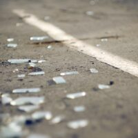 The shards of automotive glass in the accident, lying on the pavement about dividing the solid lines on the roadway